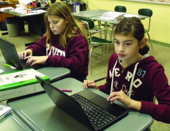 Educations-Invisible-Revolution-2girls-each-work-onlaptops